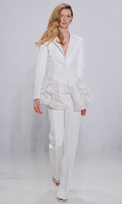 <b>Christian Siriano</b> presented a look with a twist on the traditional – a structured peplum jacket with voluminous frills. The unexpected touch is just enough detail to transform a business staple into a romantic wedding look.  