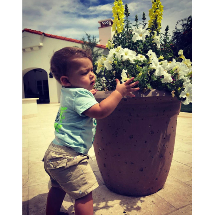 "Looks like Boomer has a green thumb! In a photo posted with the caption, ""I love being outside!!!! #peaceful,"" the eleven-month-old held on to a plant of flowers.