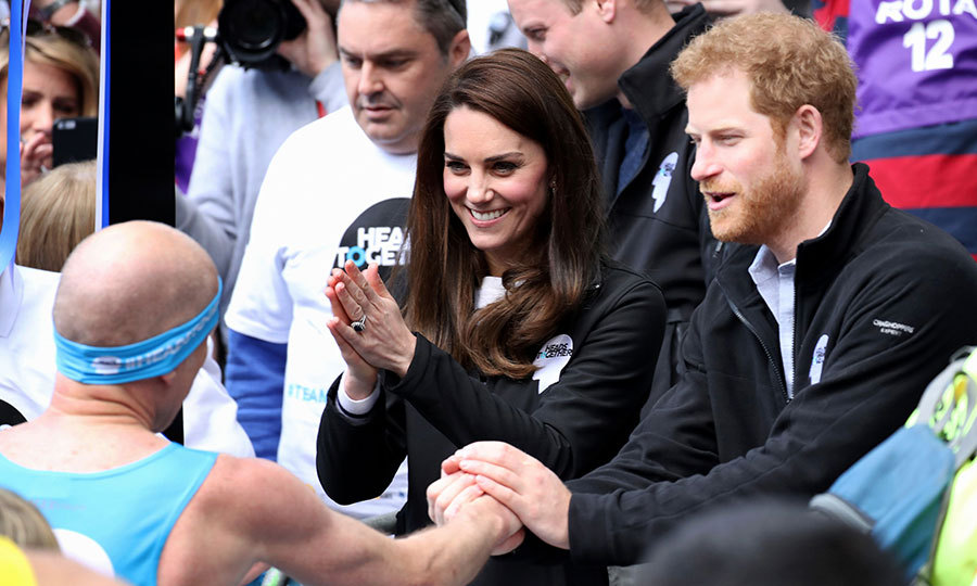 Prince Harry shook hands with a runner sporting the Heads Together headband as the Duchess applauded.