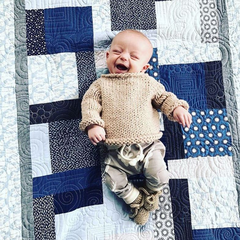 The littlest of the Kelley clan sure had one big smile as he posed on a quilted blanket in comfy attire.