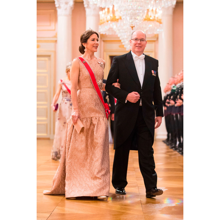 Crown Princess Mary wore a gold-patterned, sleeveless gown to Norway's King and Queen's joint birthday celebration. She accessorized with a gold sequined clutch and a tiara from the Danish royal collection. 