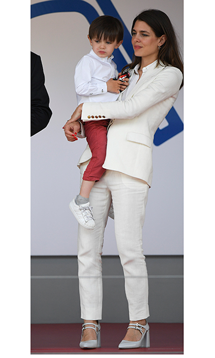 Princess Grace's granddaughter Charlotte Casiraghi looked cool in a white linen suit as she held her son Rafael during the Monaco Formula E Grand Prix in Monte-Carlo.