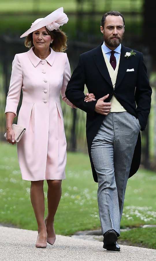 Mother-of-the-bride Carole Middleton was pretty in pink as she arrived on the arm of son James Middleton.