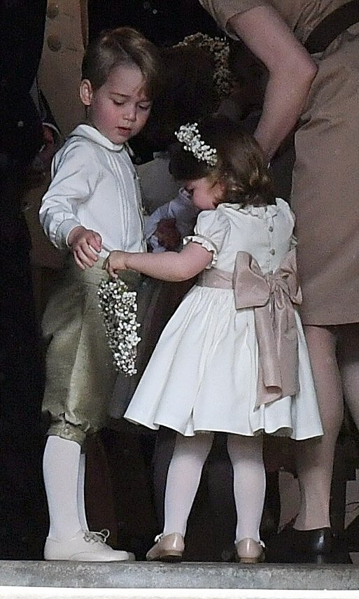 Big brother Prince George helped his little sister Princess Charlotte with her flower girl duties as the two little royals entered the church.