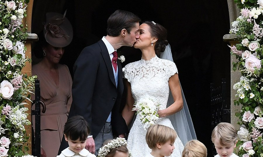 Standing under the archway, decorated with dusty rose-colored blooms, the newlyweds shared a kiss.