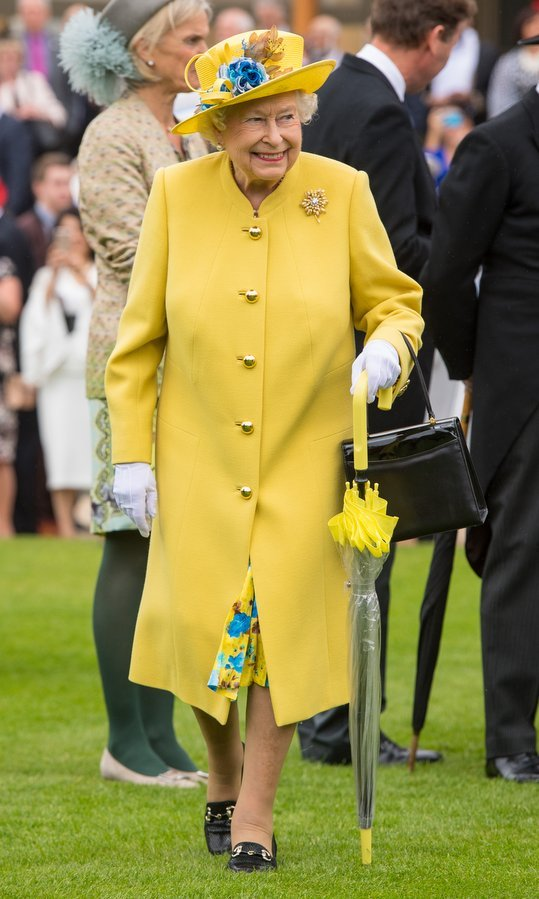 Queen Elizabeth brought her own dose of sunshine in a canary yellow outfit – complete with matching umbrella! – as she hosted a garden party at Buckingham Palace.