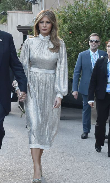 Melania Trump stepped out in her second Dolce & Gabbana dress of the day in Taormina. The first lady wore this t-length shimmery dress with billowy sleeves to a concert of La Scala Philharmonic Orchestra at the ancient Greek Theatre.