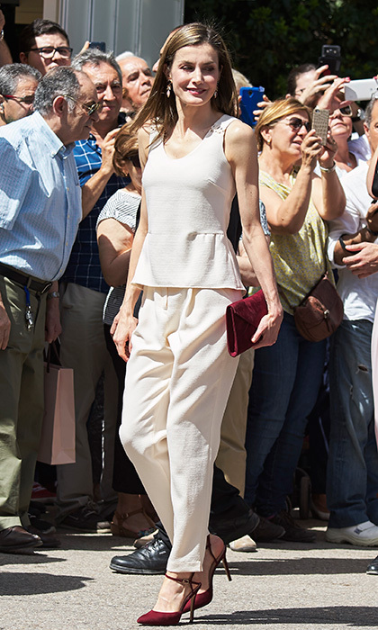 Queen Letizia added a burgundy clutch and heels to her summer-ready cream-colored outfit worn to the Madrid Book Fair in Retiro Park.