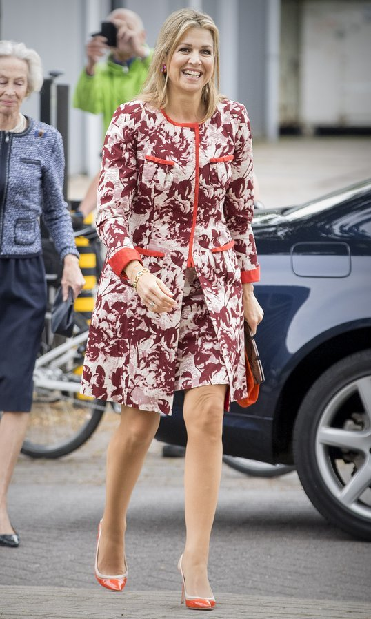 When it comes to bright hues, Queen Maxima of the Netherlands always comes through! The Dutch royal wore this matching printed coat and dress – given added pops of color with her orange shoes, purse and trim! – at Tobroco Machines in Oisterwijk, Netherlands on June 8.
