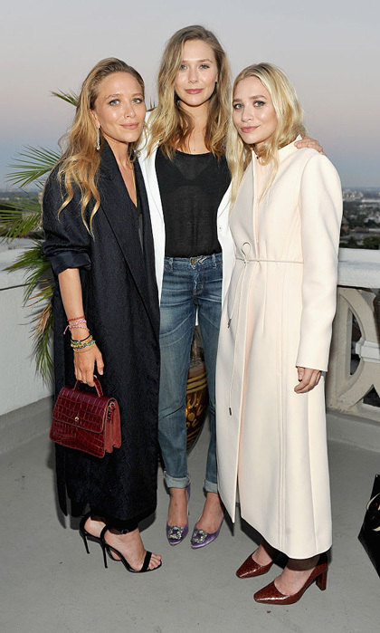 Both sisters opted for trench coats as they posed with their younger sibling Elizabeth at the Elizabeth and James flagship store opening with InStyle at Chateau Marmont in West Hollywood in July 2016.
