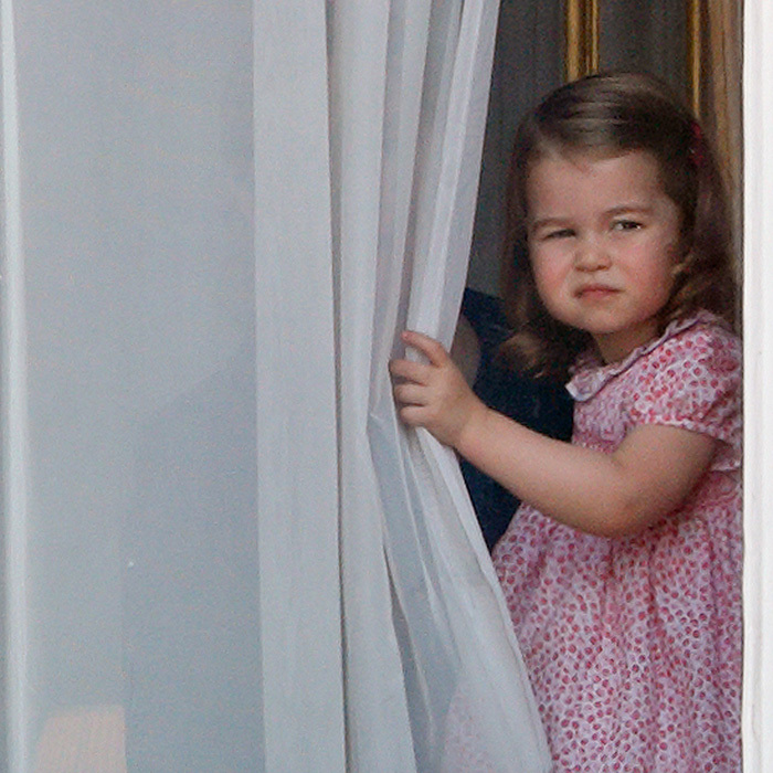 Adorable Princess Charlotte took a peek from behind the curtains at Buckingham Palace to check out the action during the annual Trooping the Colour parade in London.
