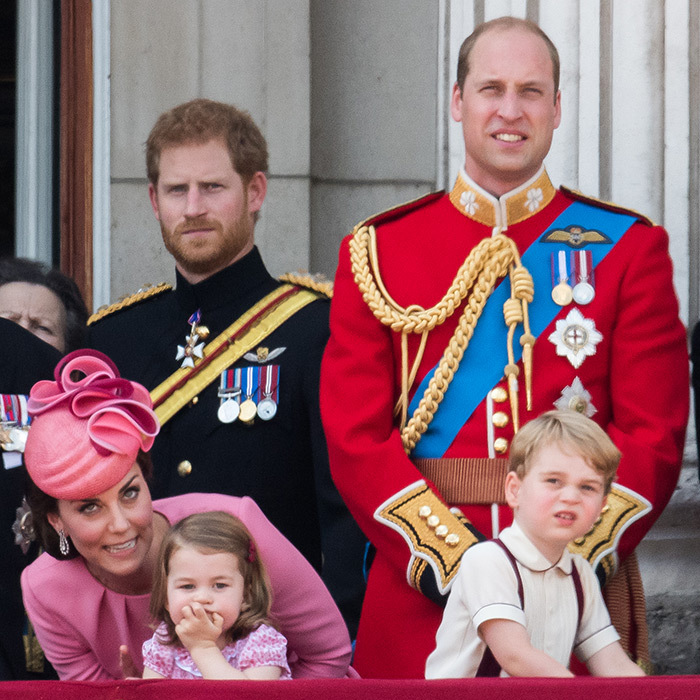 As the guys – Prince Harry, Prince William and Prince George – looked on, Duchess Kate whispered to little Princess Charlotte during Trooping the Colour. 