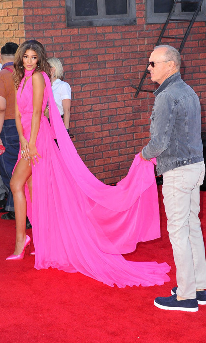 Batman star Michael Keaton shadowed as a train holder for Zendaya during the <i>Spider-Man: Homecoming</i> premiere in Hollywood.