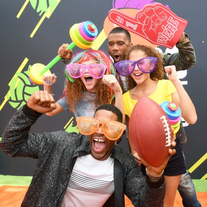 Say cheese! Kids Choice Sports awards host Russell Wilson had some fun with Michael Strahan and his two girls on the orange carpet.