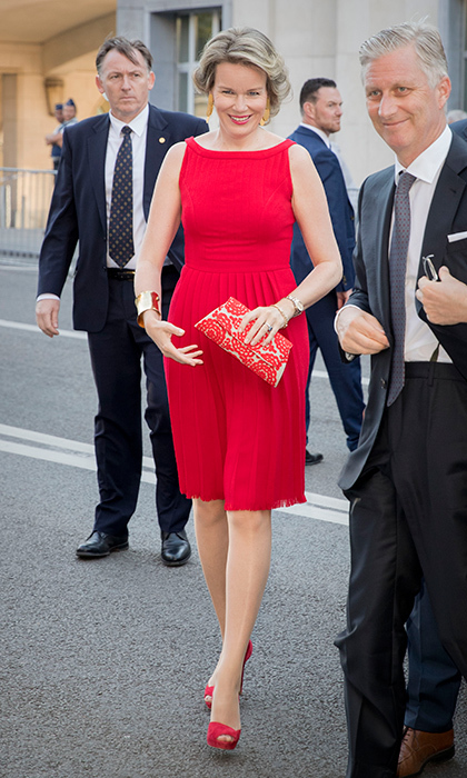 Queen Mathilde of Belgium accessorized her red pleated dress with a patterned clutch and peep toe shoes when she stepped out in Brussels for a concert on the eve of Belgian National Day.