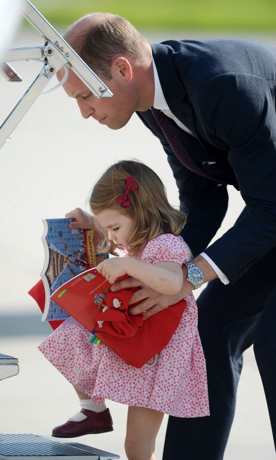 Getting a hand from her dad Prince William, little Charlotte had her hands full as she embarked for the flight home to England at Hamburg airport on July 21.