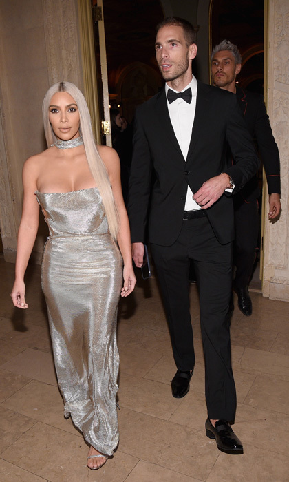 Kim Kardashian, with best friend Simon Huck, channeled her inner Donatella Versace with her newly-dyed hair and Versace gown at the party.