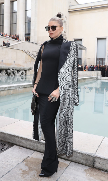 The 'Dutchess' touched down in Paris. Fergie wore a black dress with a patterned coat to the Rick Owens show.