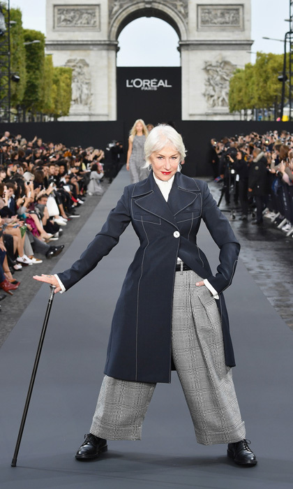 Helen Mirren dominated the L'Oreal Paris runway in a buttoned coat and wide-legged trousers with a walking stick.