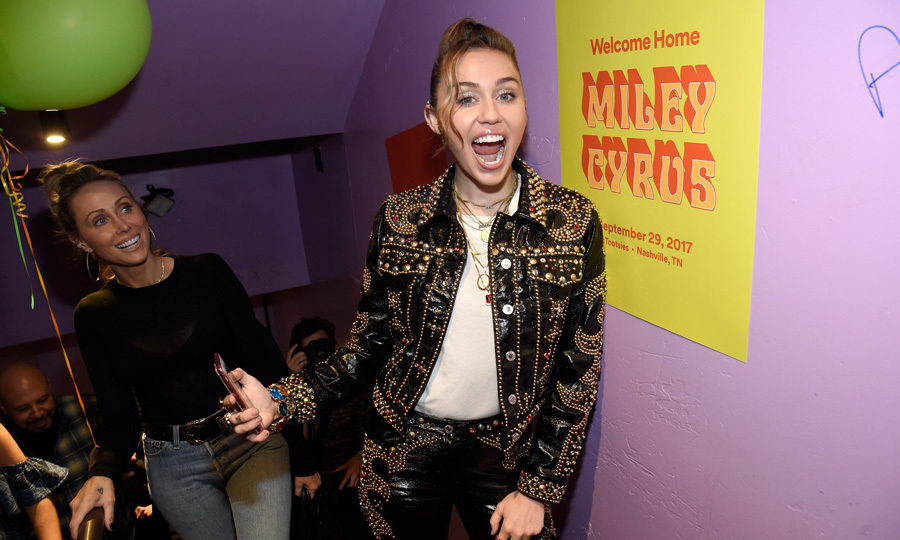 Miley Cyrus returned home to Nashville to perform an hour-long set at the #SpotifyFansFirst party. The singer, with her mom Trish and dad Billy Ray, answered questions, sang and kicked off the album release for <I>Younger Now</I> at famed honky-tonk bar Tootsie's. 