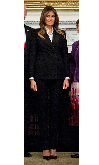 The first lady embraced the fall season's masculine trend in a sharply-tailored black trousersuit worn with a crisp white button-down shirt. Pointy-toed pumps completed the look. Melania donned the businesslike look for her husband's meeting with senior military leaders and spouses after a briefing in the State Dining Room of the White House on October 5.