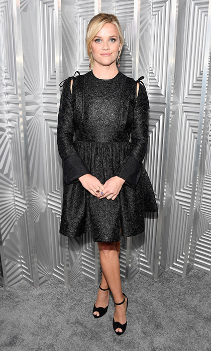 Reese Witherspoon wore a long-sleeved sparkly LBD by Calvin Klein to the Women in Hollywood party in Beverly Hills. The dress featured peek-a-boo shoulders and a pleated waistline.