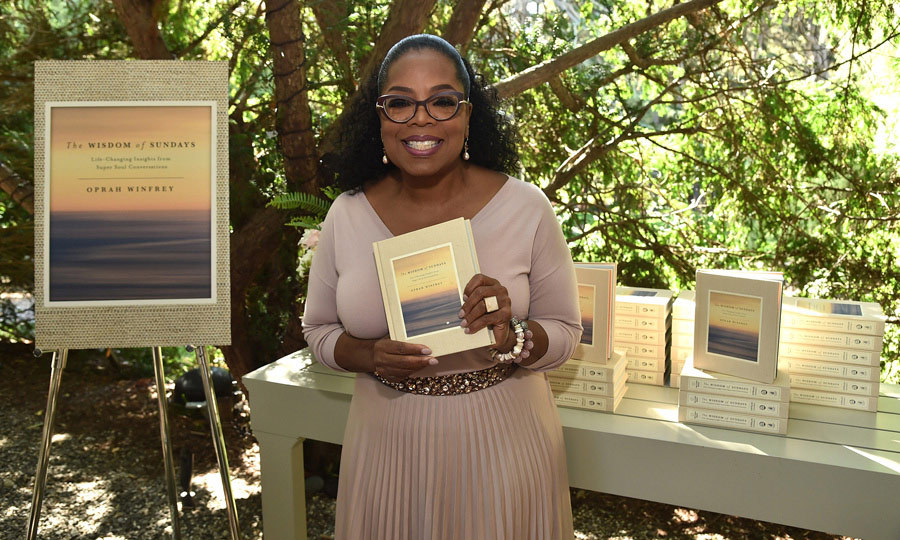 Everybody gets a book! Oprah Winfery couldn't help but smile as she held up her brand new book <I>Wisdom of Sundays</I> during her annual Gospel Brunch celebration held at her home in Montecito, California. The star-studded event included Julia Roberts, Kerry Washington, Common and many more.