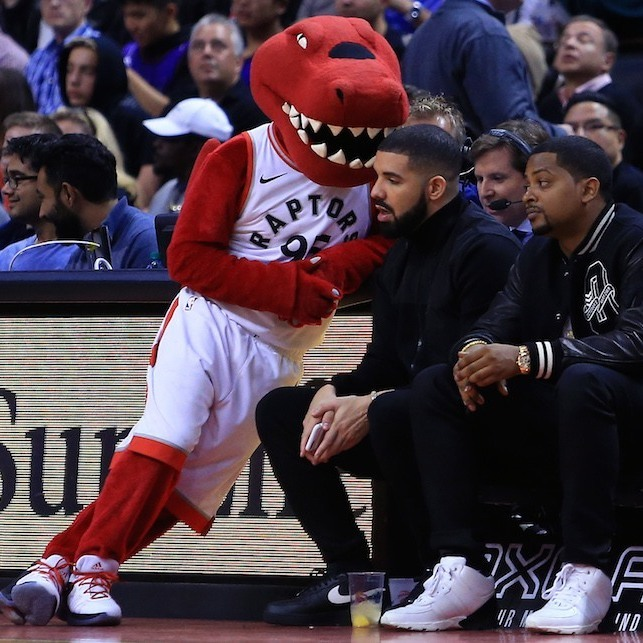 A rapper and a raptor! Drake sat courtside at the Air Canada Centre for the Toronto Raptors' game against the 76ers on October 21. The Raptor took a break from entertaining the crowds at the ACC to catch up with Drake, just 3 days prior to the rapper's birthday.
