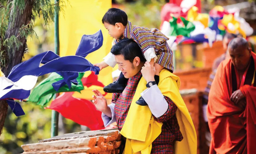"The little Prince and his dad enjoyed a colorful outing on October 30, 2017. The photo is featured as the November image from Yellow. Along with the image that was shared on both King Jigme Khesar Namgyel Wangchuck and Queen Jetsun Pema's Facebook pages, the caption read: ""This wonderful photograph was taken at the Dechenphu Lhakhang, which is a sacred temple dedicated to Ap Genyen, one of the most important protector deities of Bhutan, on 30th October, during the Dechenphu Tshechu, which is a festival dedicated to the deity.""