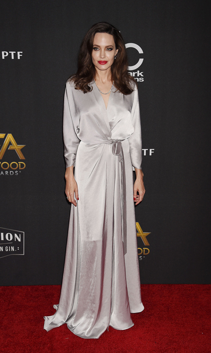 Angelina Jolie wore silver satin dress by Kate Middleton's favorite Jenny Packham to the Hollywood Film Awards on November 5. The <i>First They Killed My Father</i> director added a red lip and a full-bodies blowout to complete the look.