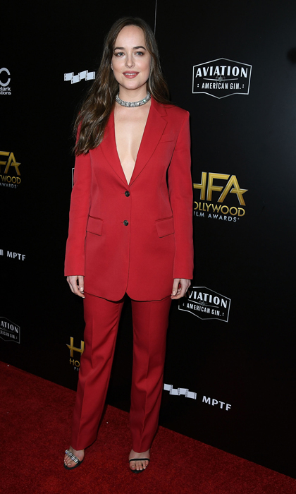 Dakota Johnson went with a crimson Calvin Klein suit to the Hollywood Film Awards. The actress accessorized with a choker and a pair of heels.