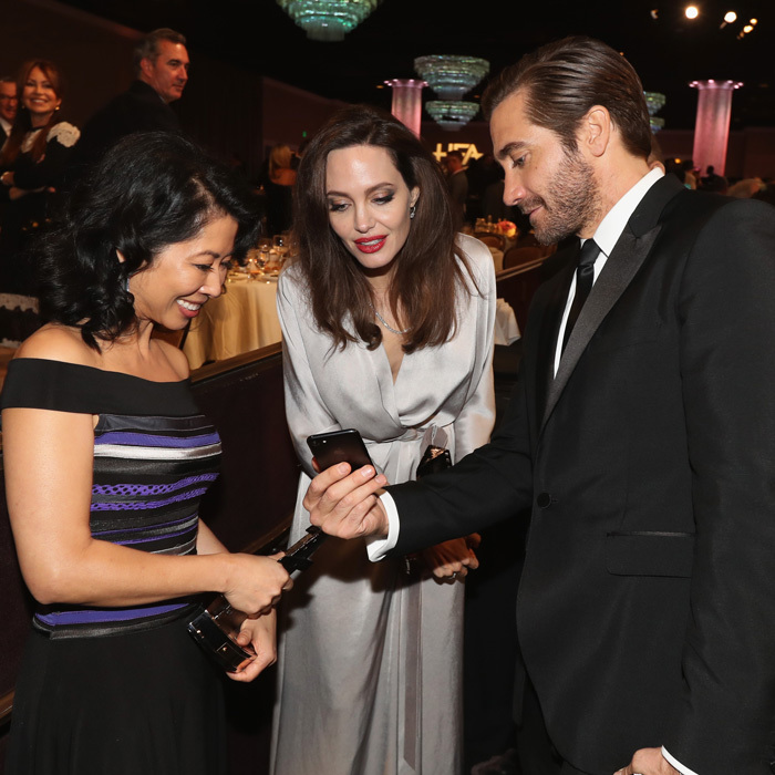 Jake Gyllenhaal showed Angelina Jolie and her producing partner Loung Ung something captivating on his cell during the Hollywood Film Awards. During the event, the mom-of-six and Loung accepted the Hollywood Foreign Language Film Award from inside the Beverly Hilton.