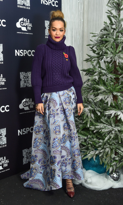 Rita Ora showed off her cold-weather style as she participated in turning on the Oxford Street's iconic Christmas Lights. The British singer wore a comfy purple sweater with a ballgown skirt and heels as she stood center stage to do the honors.