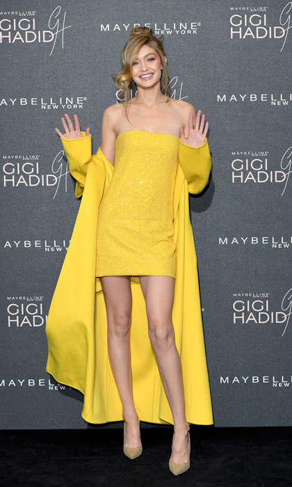Gigi Hadid was a ray of sunshine at her GigixMaybelline party in London. Arriving to 'Hotel Gigi', the supermodel wore a yellow Ralph Lauren strapless mini dress with a matching trench coat.