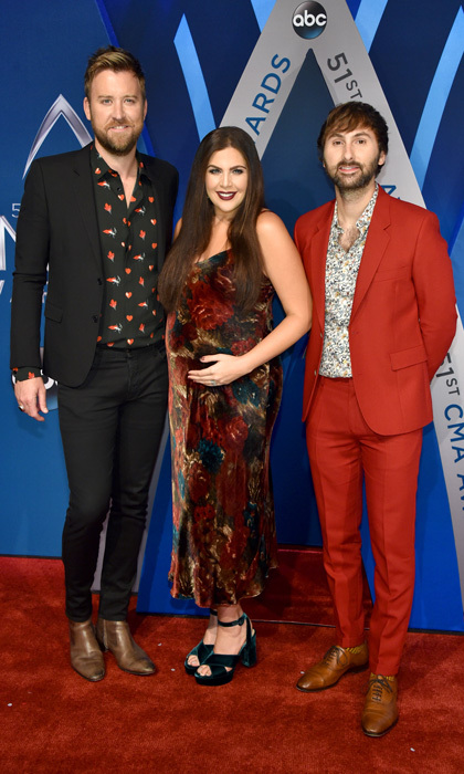 "Lady Antebellum's Charles Kelley, Hillary Scott and Dave Haywood gave autumnal vibes for their red carpet look. The pregnant singer even took to Instagram to comment on her look. She wrote: ""Velvet is one of my absolute favorite trends this season and a huge thanks to @ilariaurbinati for finding this @poloralphlauren slip dress. We took a little bit of an ""anti-red carpet gown"" approach this year and it was so fun! Thank you @evolution_man and @lindsay.doyle for the glam and @cdittmer for getting me dressed for the night.""