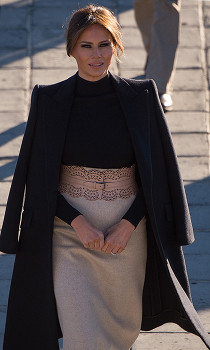 Melania looked impeccably chic for her last day in Asia pairing her nude flats with a black turtle neck, grey high-waisted pencil skirt, beige leather belt and a black coat draped over her shoulders.