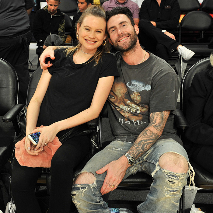 Cute couple alert! Adam Levine and model wife Behati Prinsloo snuggled up during the Los Angeles Lakers vs Philadelphia 76ers NBA match at Staples Center on November 15 in Los Angeles. The couple announced in September that they're expecting baby #2. 
