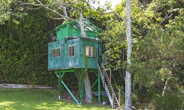 A tree house in the backyard blends seamlessly with its surroundings thanks to a forest-green paint job. (Image: MLS)