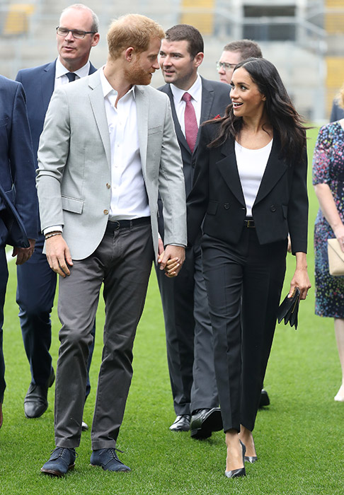 Prince Harry and Meghan holding hands.