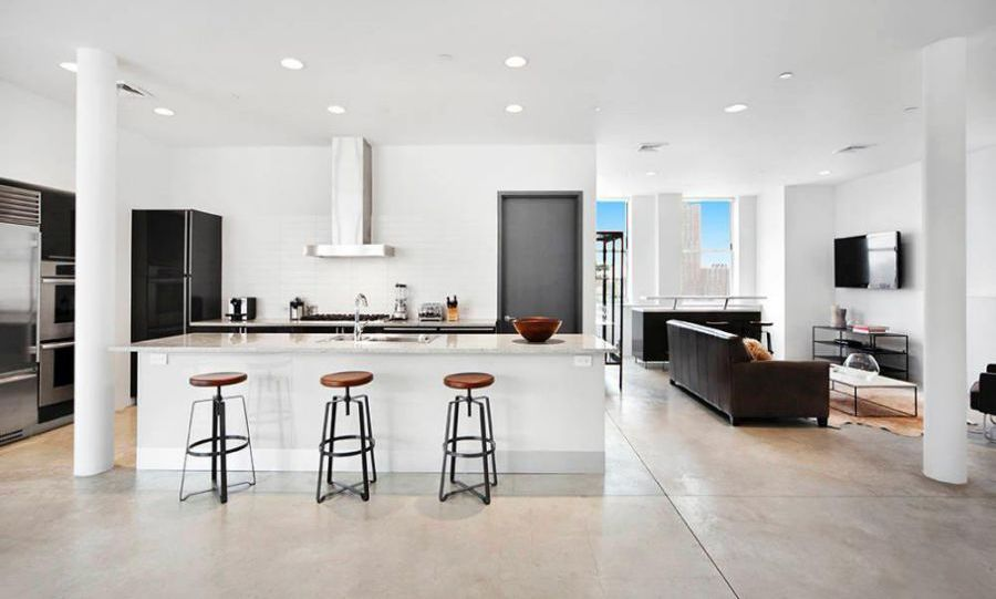The modern chef's kitchen is fitted with Val Cucine cabinetry and top-of-the-line appliances, including a Sub Zero refrigerator and wine cooler. The apartment is perfect for entertaining thanks to its open plan layout and incredible terrace, where there is currently an al freso dining table and sofa.