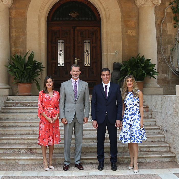 The King and Queen of Spain met with Prime Minister Pedro Sanchez and his wife, Maria Begona, at Marivent Palace on Aug. 6. Letizia stunned in a bright Adolfo Dominguez coral floral print dress and her favourite pair of Steve Madden 'Plaza' mules.