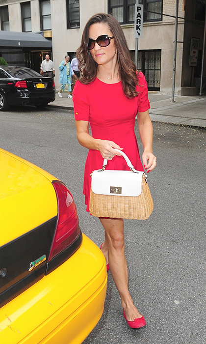 Pippa accessorized this cherry red ensemble with her wicker handbag.