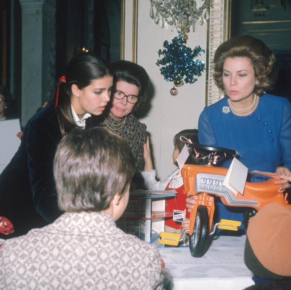 Young Caroline handed out Christmas presents to needy kids with mother Grace Kelly in 1971. 