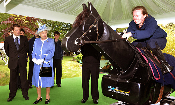 Her Majesty examines a mechanical horse used to train jockeys, during a 2011 visit to Ireland