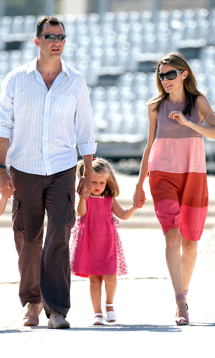 The little royal stayed cool in a rosy dress that matched her little sister's – and complemented mom Queen Letizia's – for a walk with her parents around the bay of the Spanish island. <br>