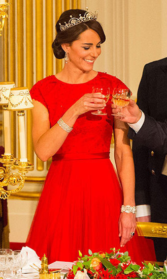 Prince George's mom wore a stunning red haute couture Jenny Packham gown to attend her first ever official state banquet. The 33-year-old accessorized her outfit with the Lotus Flower royal heirloom tiara.<br>