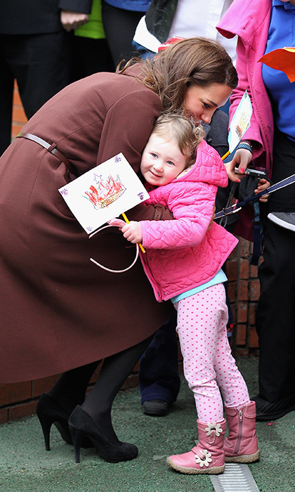 A little princess waiting outside the Alder Hey Children's NHS Foundation Trust shared a special moment with the Duchess of Cambridge during her visit to the center in 2012.