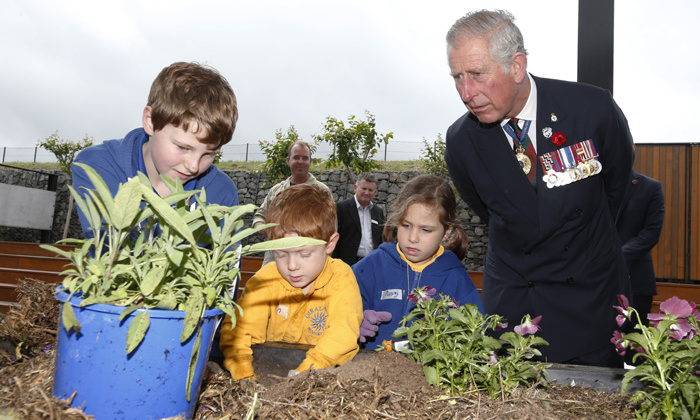 Prince George's grandad joins in with a children's gardening activity in the Discovery Garden at Australia's National Arboretum.