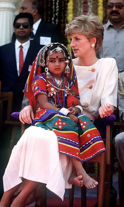 In Hyderabad, Princess Diana of Wales sat with a local girl who wore traditional costume during a visit to Lallapet High School.