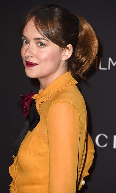Dakota Johnson proves a ponytail isn't just for daytime, with her brunette locks in a 1960s style with slight volume at the crown and bangs swept to the side. 